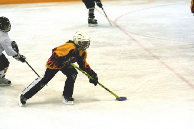 Ringette player moves the ring down the ice during a game. Public domain