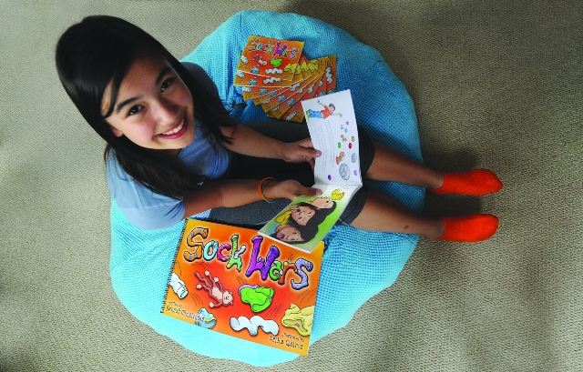 "Hannah Christensen sits with her book for children"" Mark Van Manen, The Vancouver Sun"