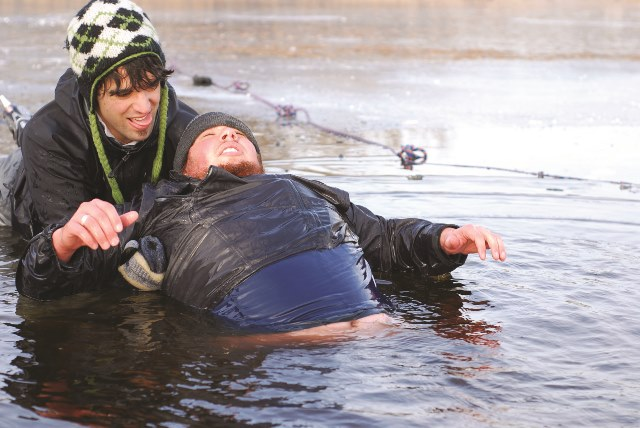 A man helps another man out of the cold water Photo: iStockphoto