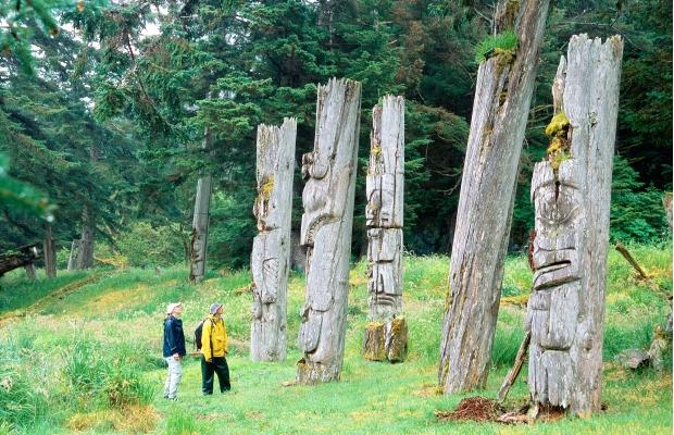 A couple looks at ancient Haida poles on Anthony Island in Gwaii Haanas National Park Reserve. Photo: PNG files