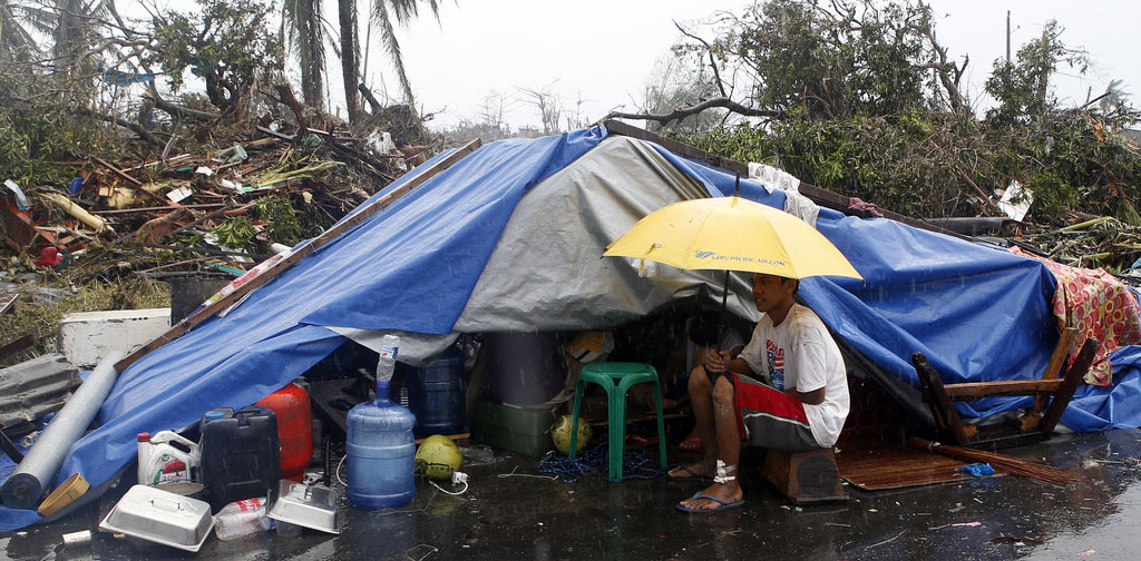 A typhoon victim sits under an umbrella outside a tent. PHOTO - MANSUNIDES / CC, FLICKR