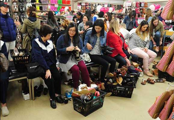 Early morning shoppers try on shoes. PHOTO – NICK PROCAYLO / PNG