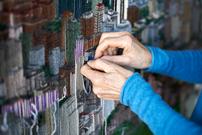 Sola paints pictures with different colours of yarn which she pulls from old sweaters. Photo by Amanda Skuse