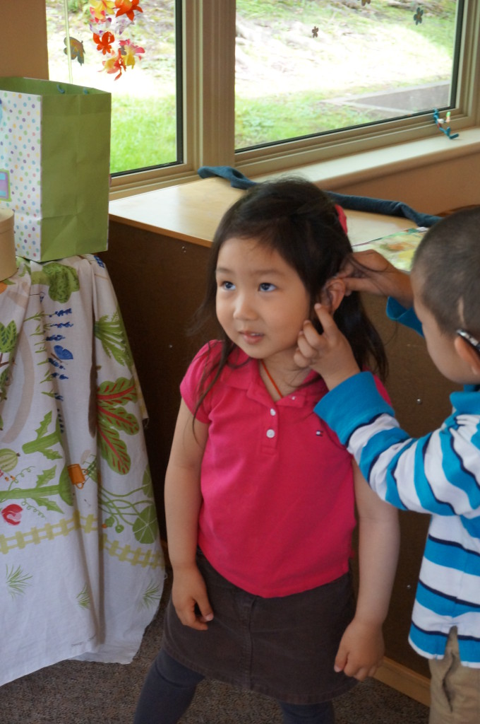 A child helps a friend with her hearing aid. Photo courtesy of CHSC