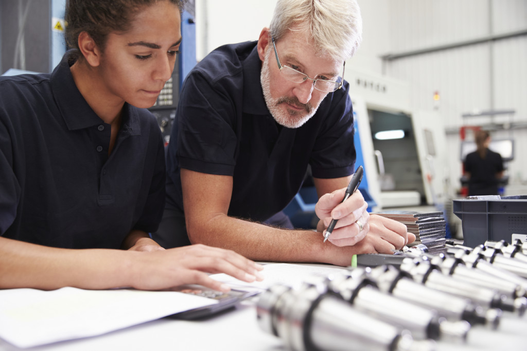 PHOTO - ISTOCK Engineer And Apprentice Planning CNC Machinery Project