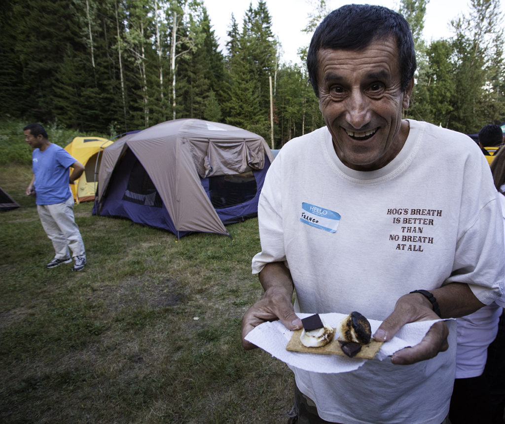 This man is holding a s'more. It's ready to eat. photo - Parks Canada / Rob Buchanan