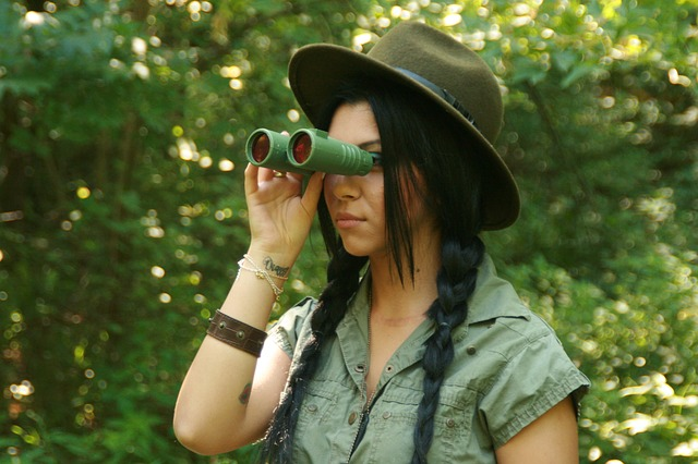 This young woman is using binoculars to look at wildlife. photo - pixabay.com