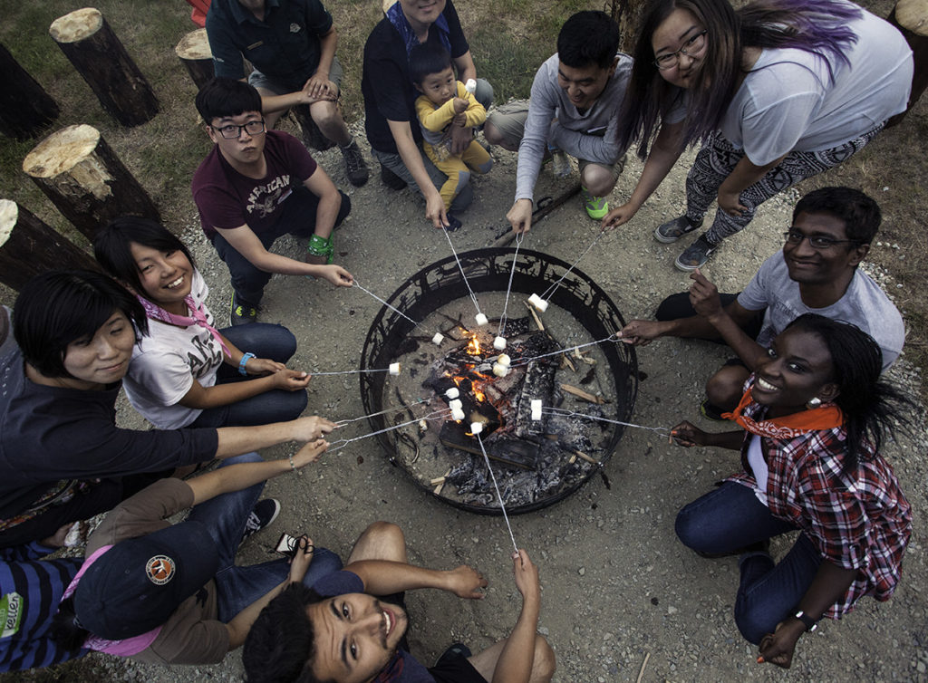 Newcomers learning to camp are roasting marshmallows for s'mores over the campfire. photo - Parks Canada / Rob Buchanan