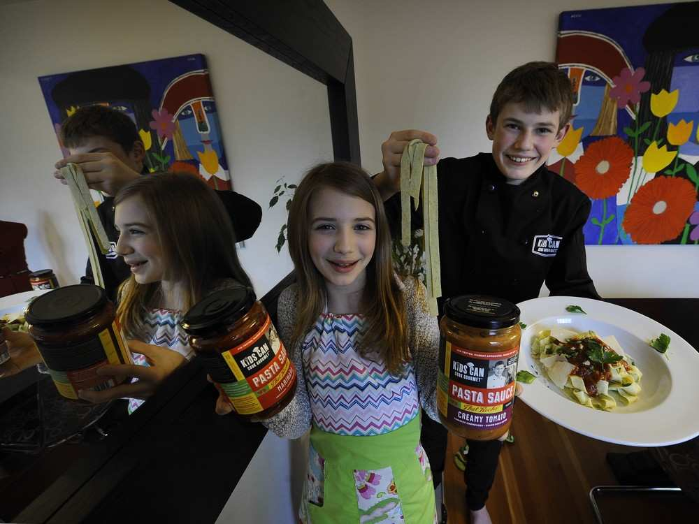 PHOTO - MARK VAN MANEN / VANCOUVER SUN Skylar and Chloe Sinow make pasta sauce.