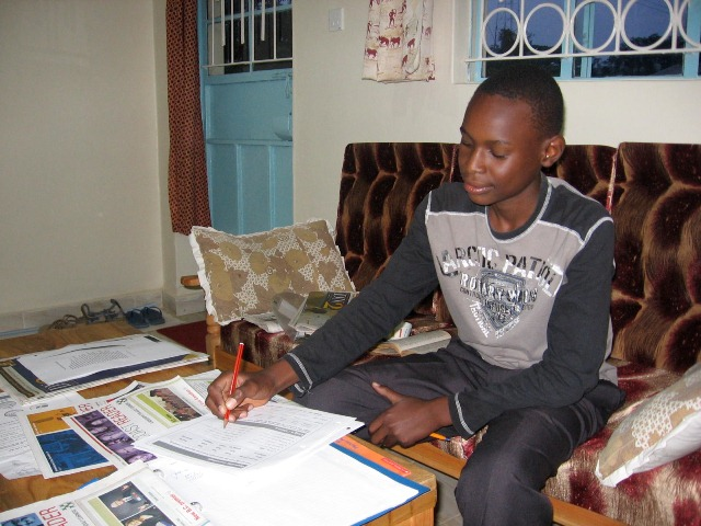 Ian Oluko, Grade 9 student in Kenya, reads The Westcoast Readerand does the student exercises. Photo by Nancy Carson
